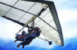 Professional hang gliding instructor and his student flying tandem off a high mountain