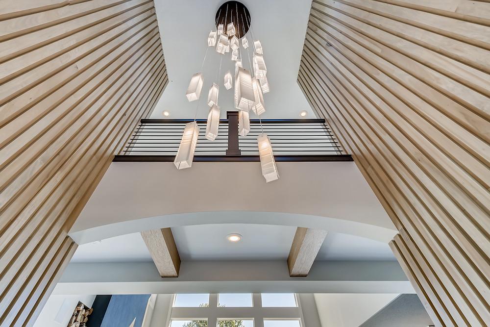 statement chandelier, wood slat feature wall, white oak beams