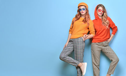 Two fashionable woman sisters in trendy orange yellow outfit, makeup. Carefree beautiful f