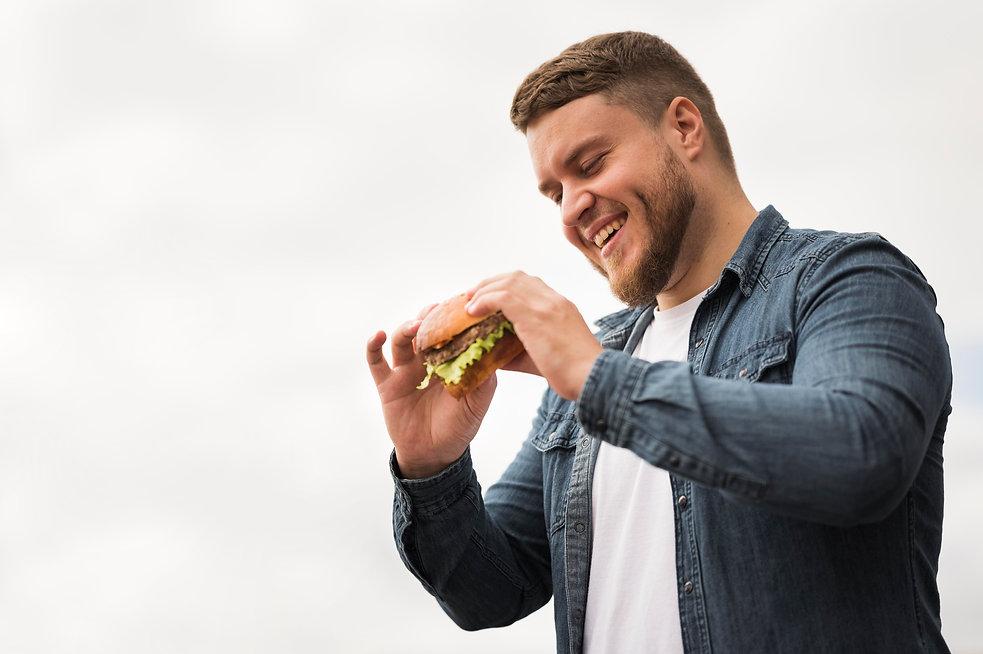 low-angle-smiley-man-holding-burger.jpg
