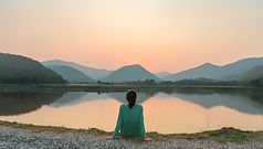 A woman is sitting at ease by the lake d