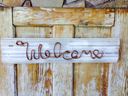 "Piece of window casing with ""Welcome"" spelled out using braided copper wire"