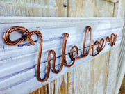 "Window casing with ""Welcome"" spelled out using braided copper wire"