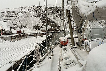 Yacht covered in snow with snowy mountains in the background