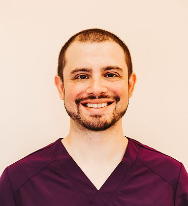 A headshot of Kyle. He is in purple scrubs against a white background. A big welcoming smile.