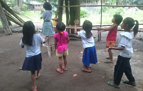 A girl standing on a chair with the other children watching her back