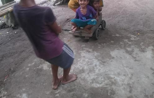 Children playing using improvised wooden cart