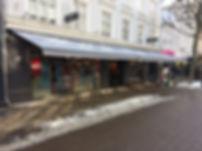 Weinor Topas markiser, monteret hos butik i en gågade. Flot grå dug, og gråt markise stel.
