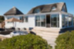 Billede af en ståtægt hus, med en stor træterrasse. På terrassen står en parasol fra Glatz.