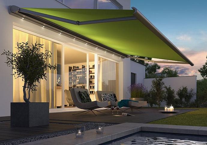 weinor Cassita med grøn dug. Markisen er udrullert, og med tændt LED belysnng, der giver en hyggelig atmosfære på terrassen.