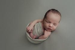 Newborn Baby Boy on Grey Huck Finn Pose Holding Foot Dayton Ohio Photographer