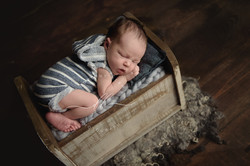 Newborn Baby Boy Laying on Bed Blue Grey Pillow on Wood Dayton Ohio Photographer