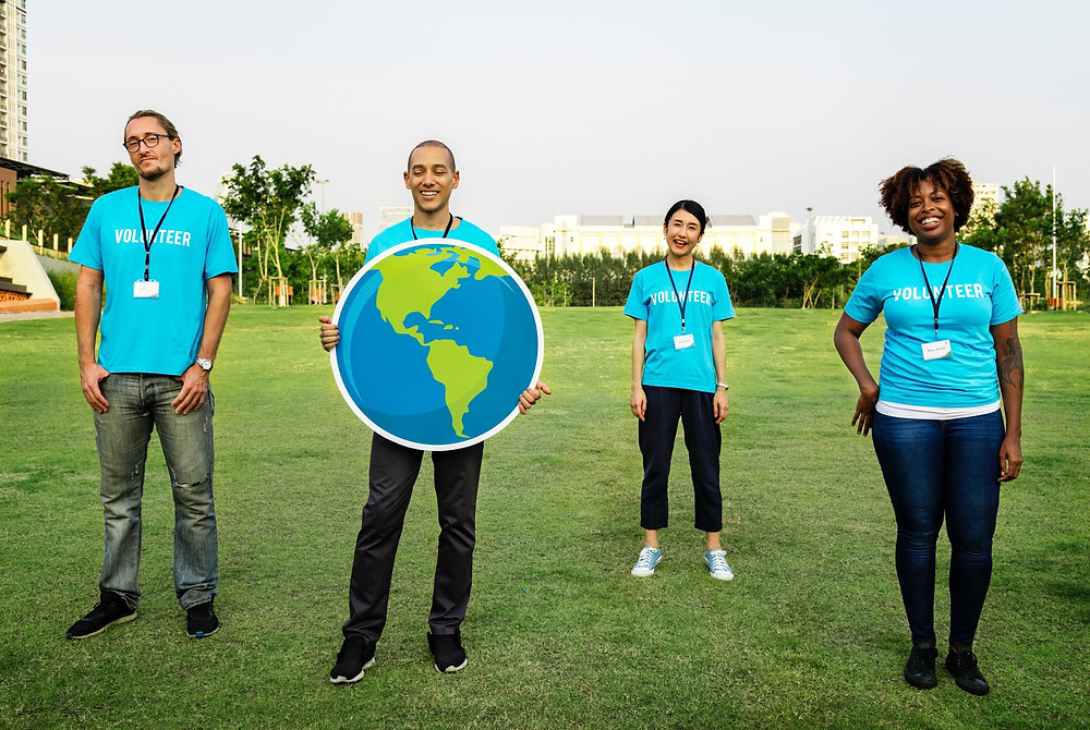 group of four people wearing blue standing on green grass field