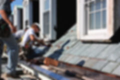 Professonal roofers repairing a roof