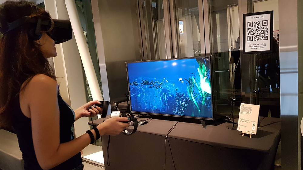 A woman standing in front of a screen wearing an oculus rift headset and holding controllers. The screen shows an underwater scene.