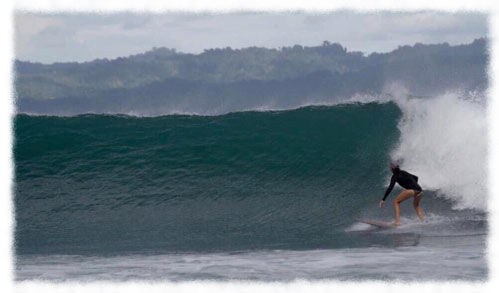 Woman surfing a large wave in the Osa Peninsula region of Costa Rica
