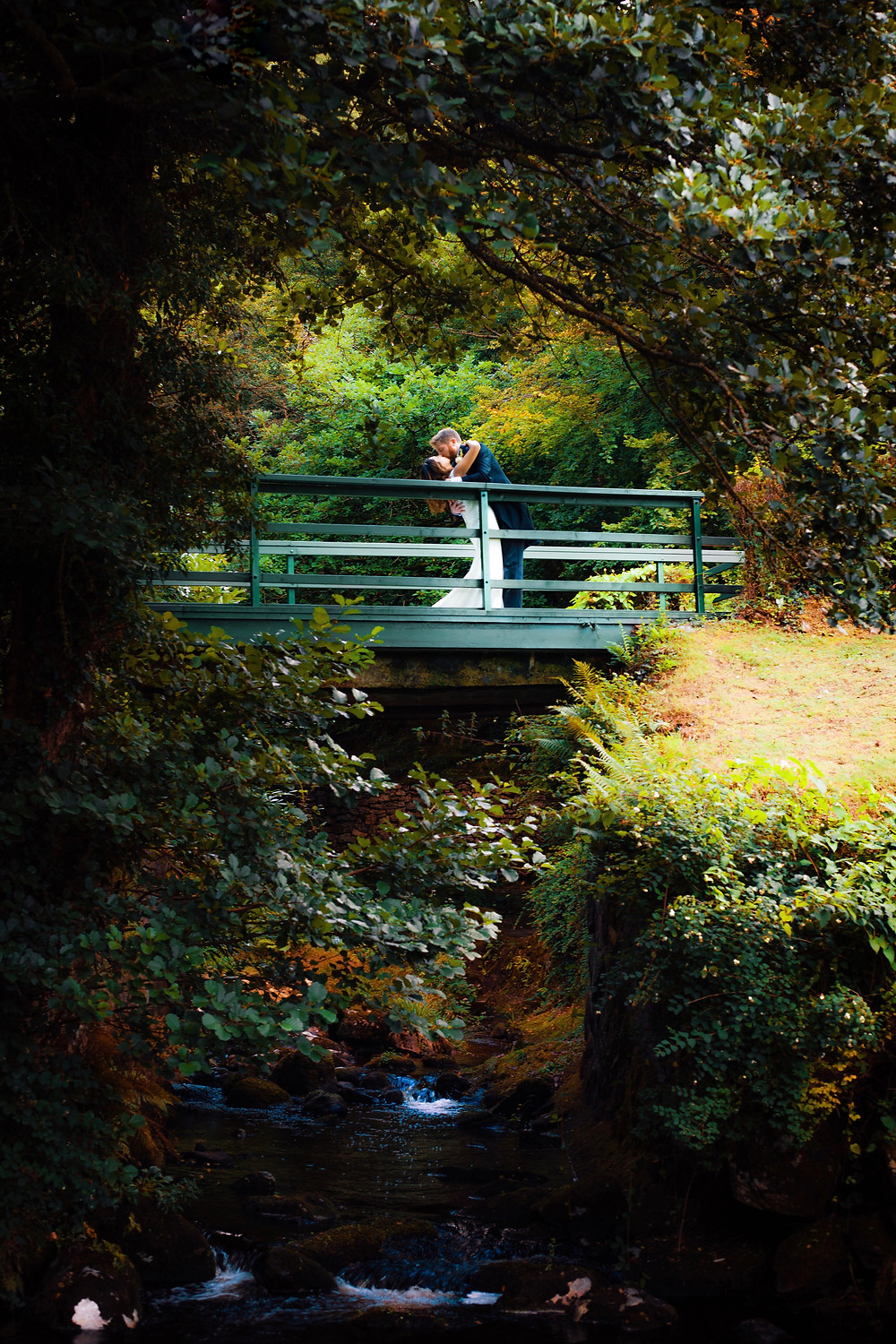 Stunning and spontaneous romantic kiss atop a bridge at Gidleigh Park on Dartmoor