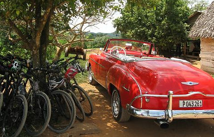 Bicycles and a red American car in Cuba
