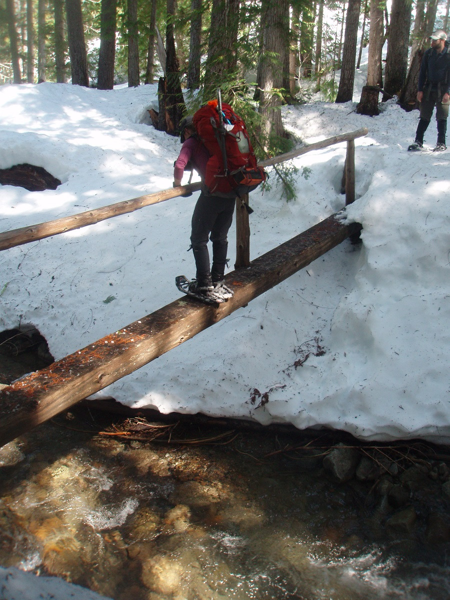 We are definitely on a trail! Crossing a boot bridge with snowshoes was part of the early season fun. Photo: Dave Golias.
