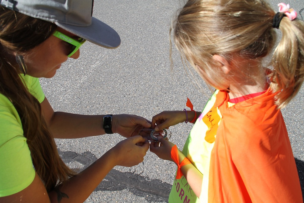 SJ volunteer Whitney helps a caped Girafficorn participant learn how to use a compass.
