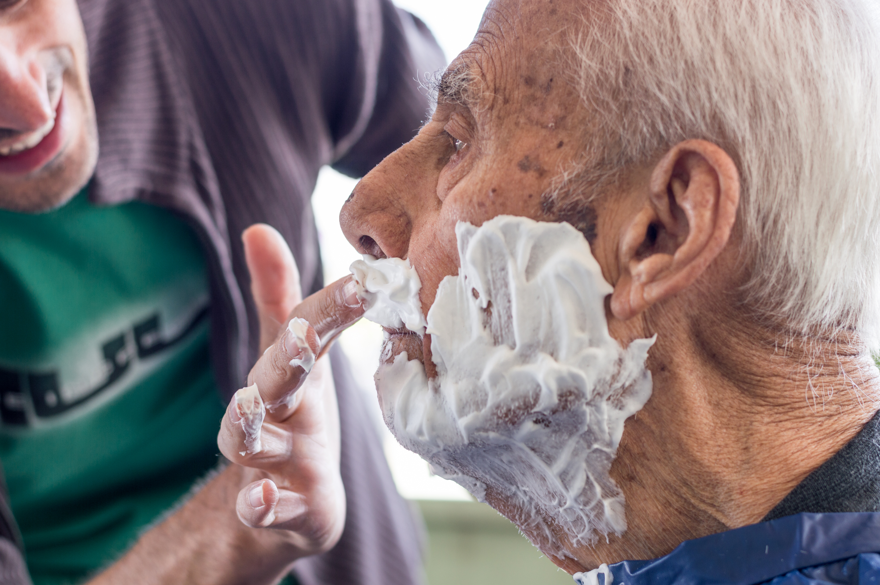 Elderly man getting his beard shaved by