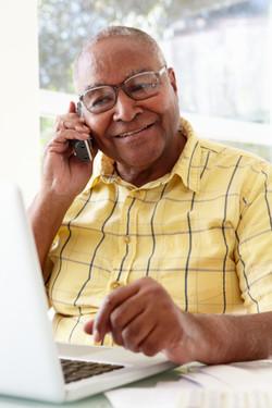 Senior Man On Phone Using Laptop At Home