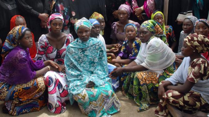 Picture taken on May 5, 2014 shows Chibok school girls who escaped from the Boko Haram Islamists gathering to receive information from officials