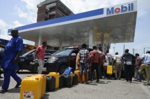 People queue with jerrycans to buy fuel at Mobil filling…