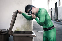 Green superhero holding his nose and ope