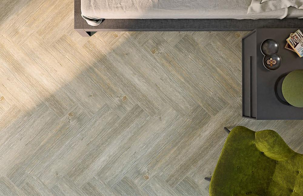 Floor made of wood look floor tiles laying in the herringbone pattern.
