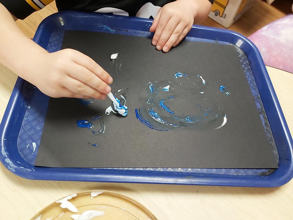 preschooler painting with eyeshadow applicator