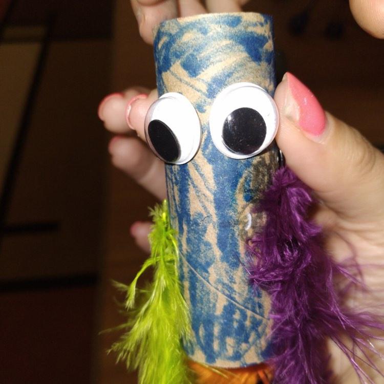 teacher holding preschooler's cardboard tube bird craft