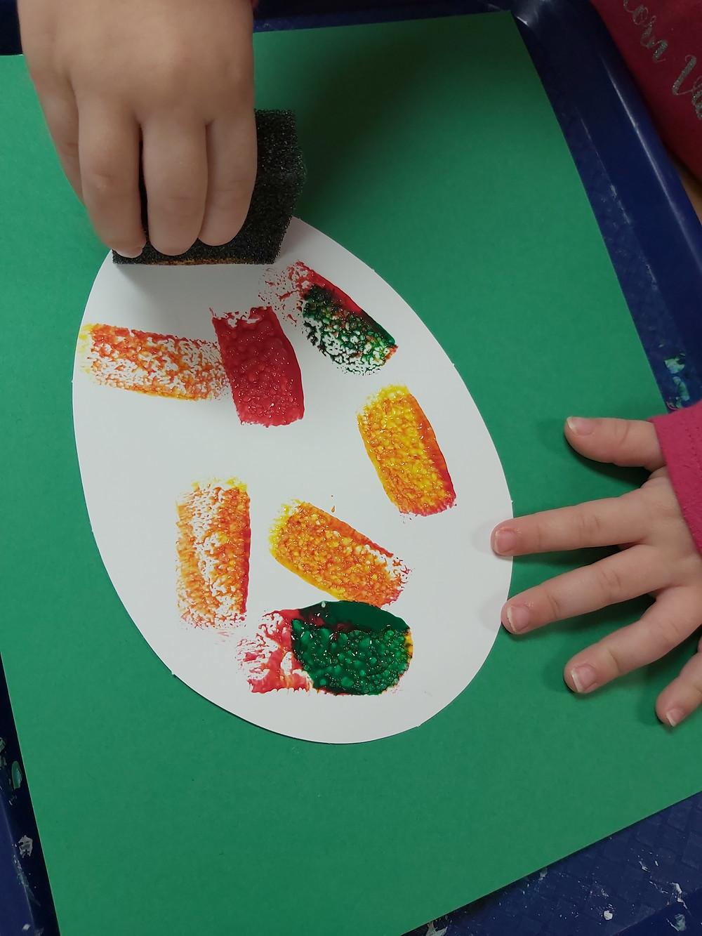 preschooler painting paper mango with sponge