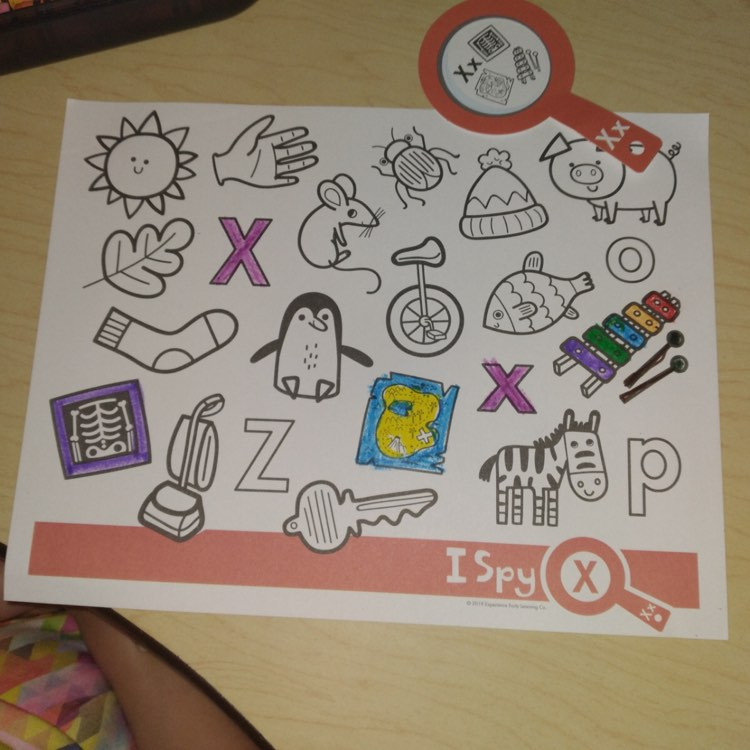 preschooler's letter X coloring page next to paper magnifying glass