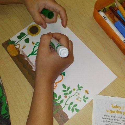preschooler using markers to make garden postcard