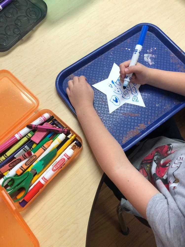 preschooler decorating paper star with markers