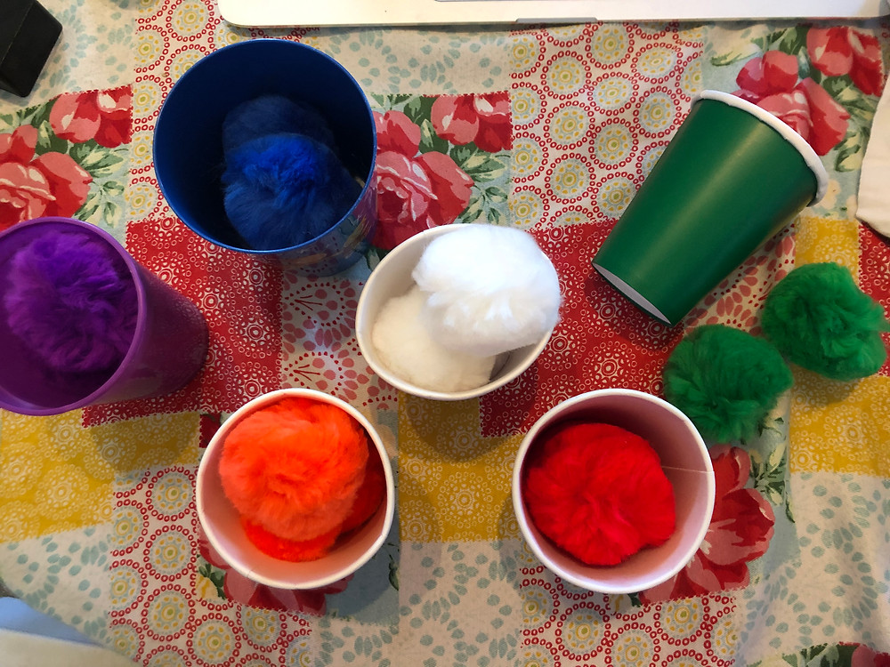 colored pompoms in cups that are the same color