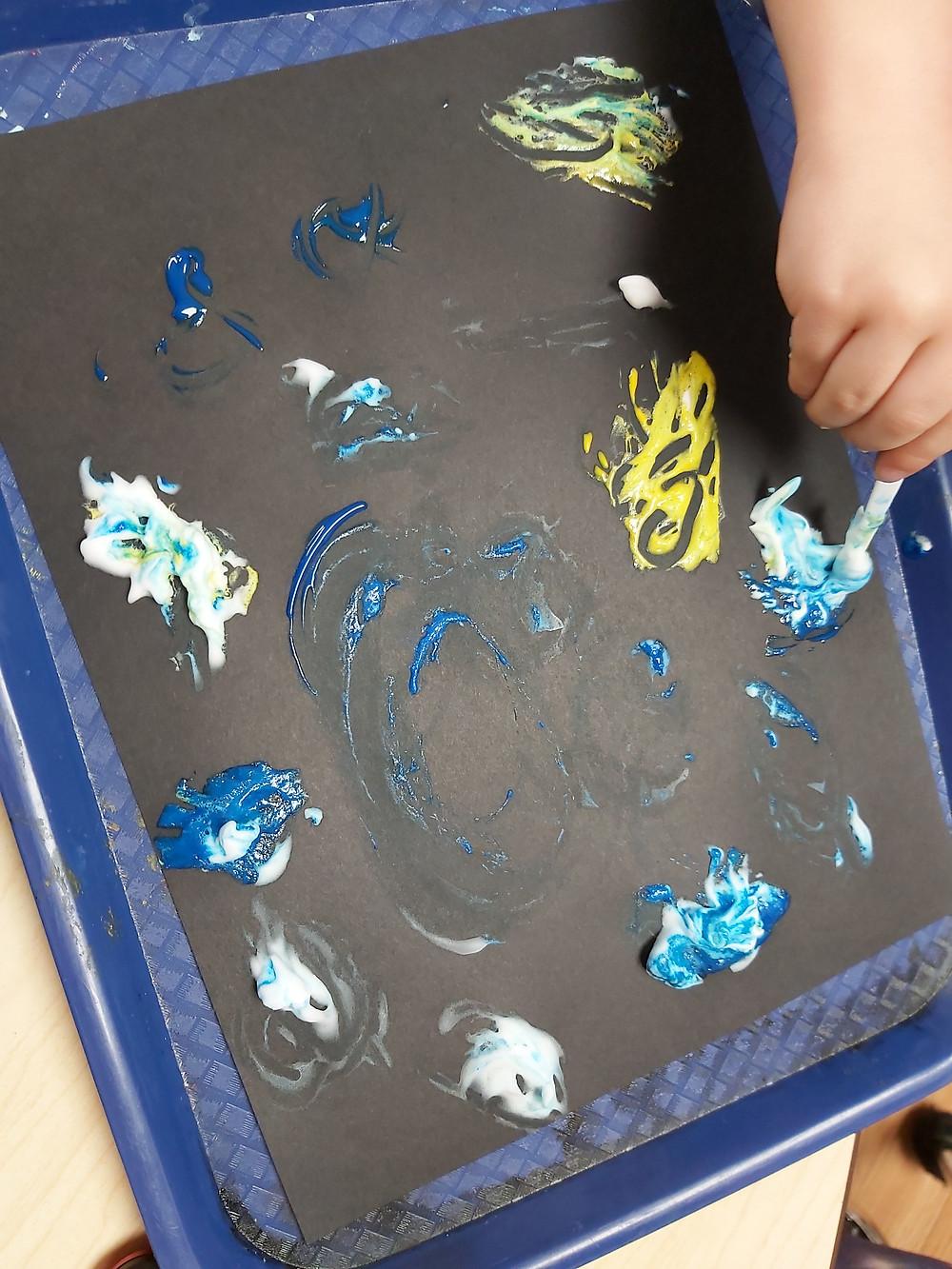 preschooler mixing shaving cream and paint on cardstock