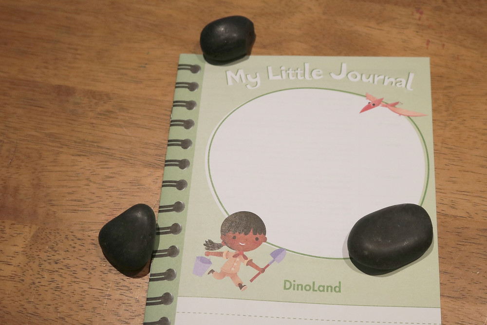 small stones next to My Little Journal on table