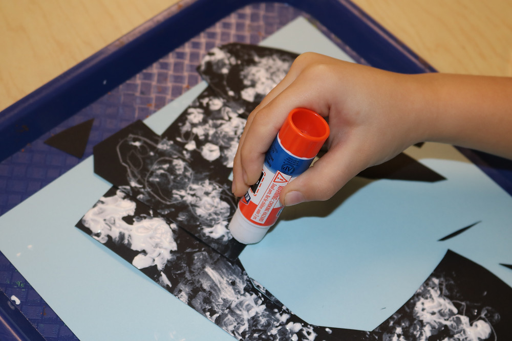 child gluing together several pieces of paper snowstorm artwork