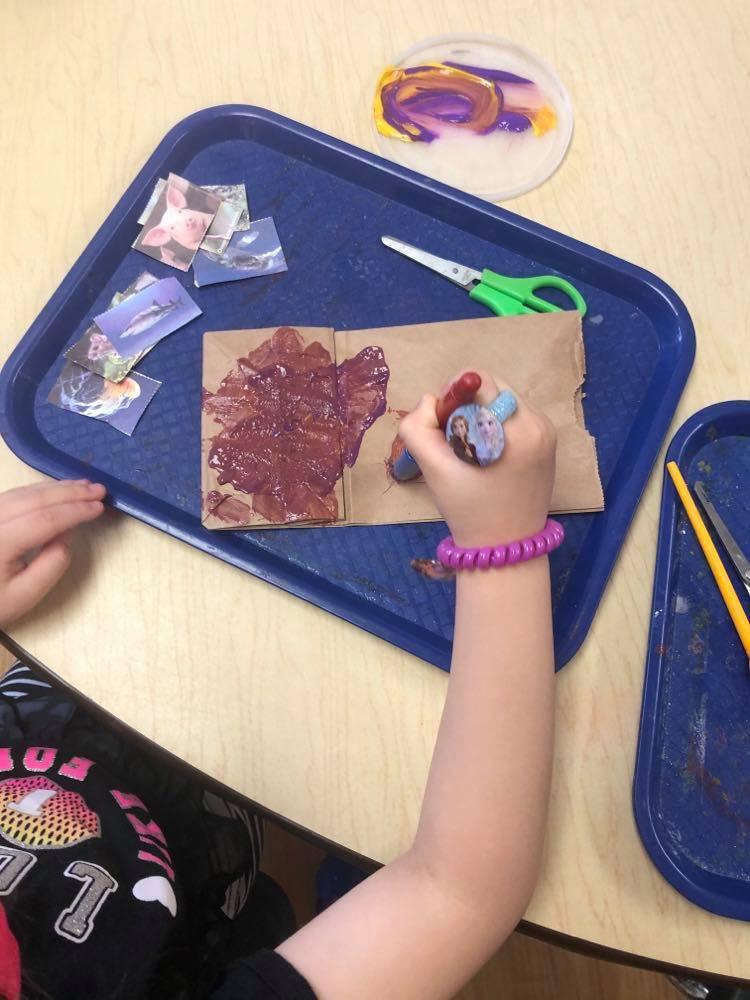 preschooler painting paper bag