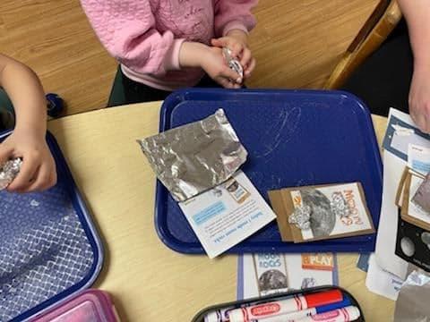 preschoolers crinkling foil into balls to make moon rocks