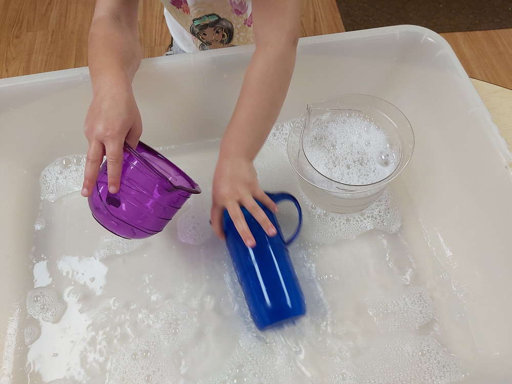 preschooler practicing measuring using water with bubbles and measuring cups