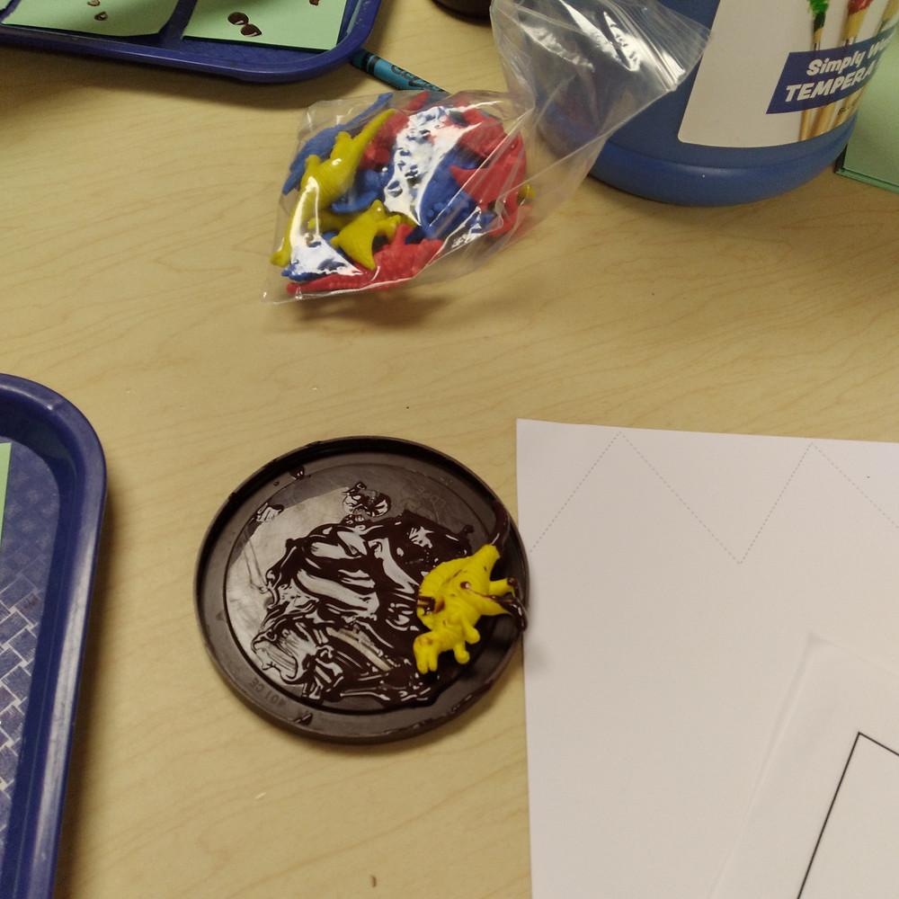 dinosaur manipulative on plastic lid with paint