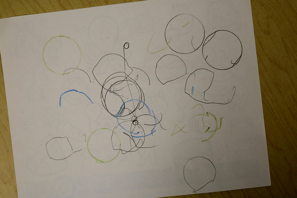 child's artwork including lots of traced circles on white paper