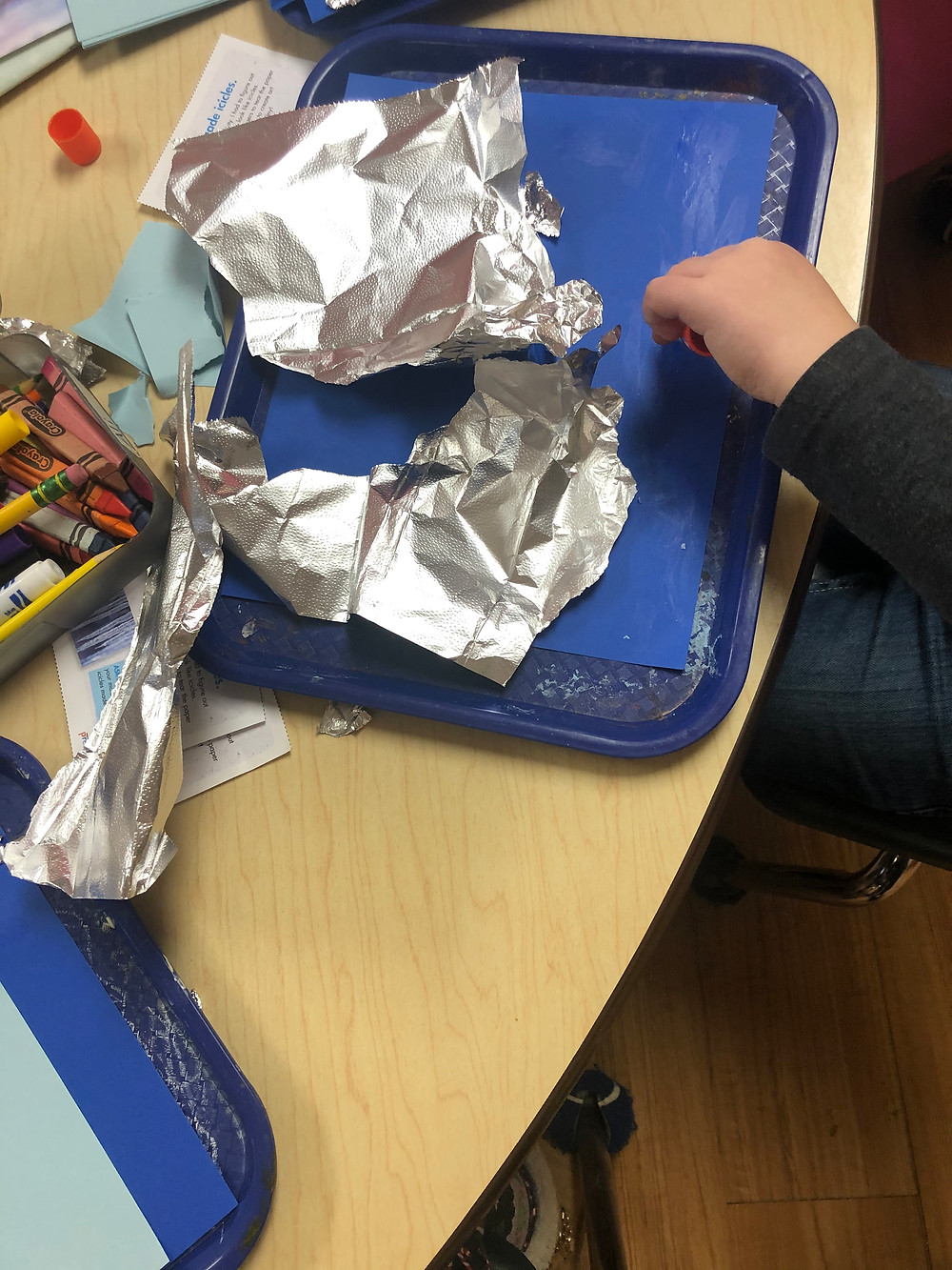 preschooler adding crinkled foil to cardstock to make icicle process art