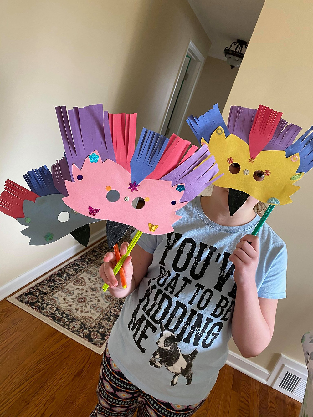 child holding one bird mask craft over face and two more bird masks in the opposite hand