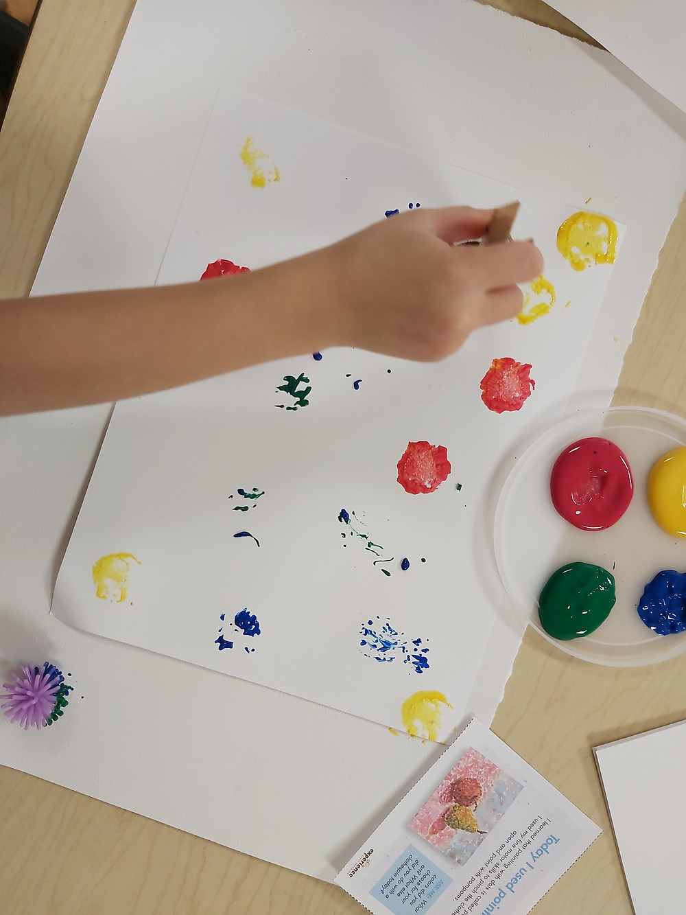 preschooler using clothespin with pom-pom to paint