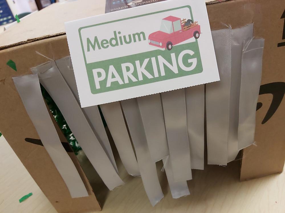cardboard car wash with sign: Medium Parking