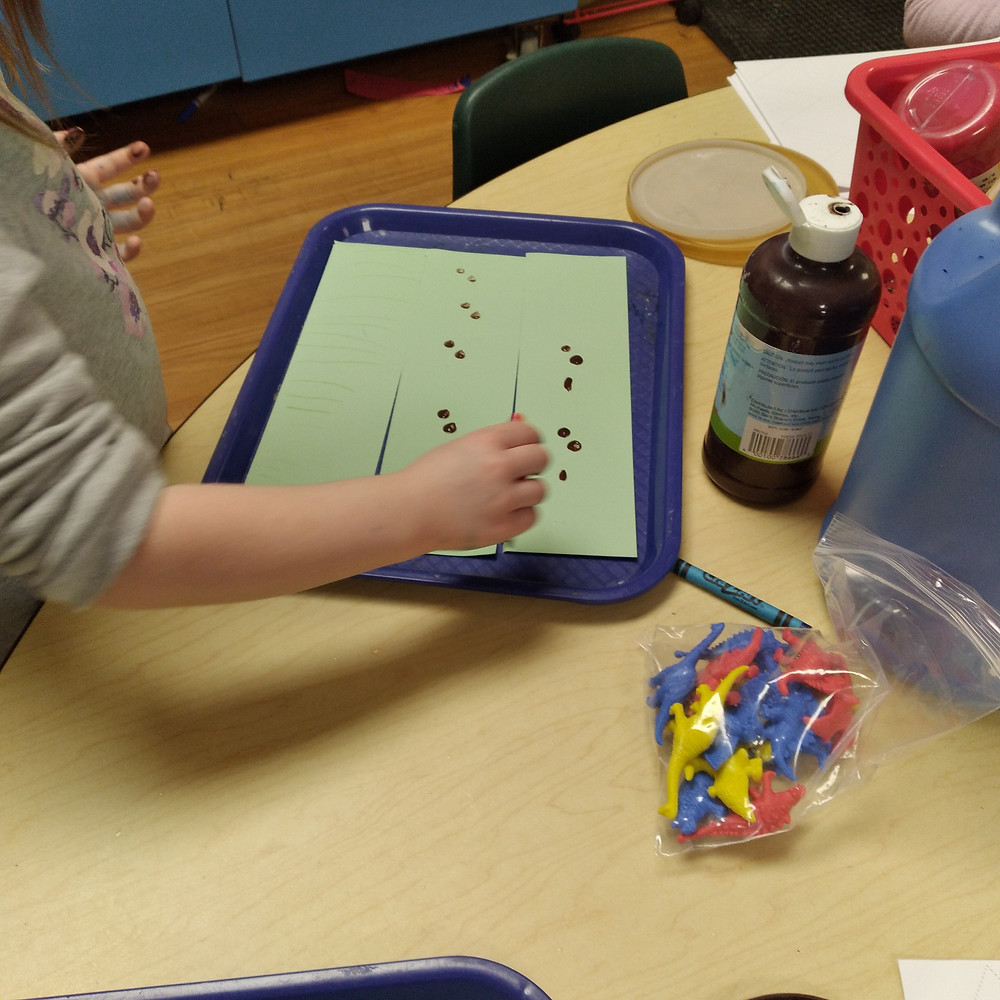 preschooler painting cardstock dino paths on tray